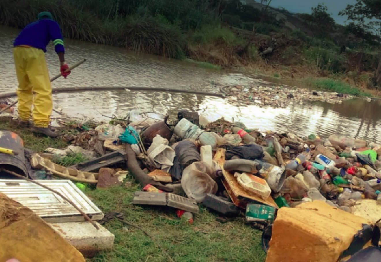 Man cleaning up trash collected by a river boom