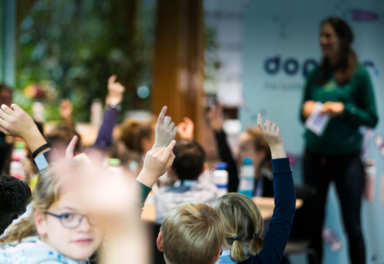 Children raising their hands up in a classroom