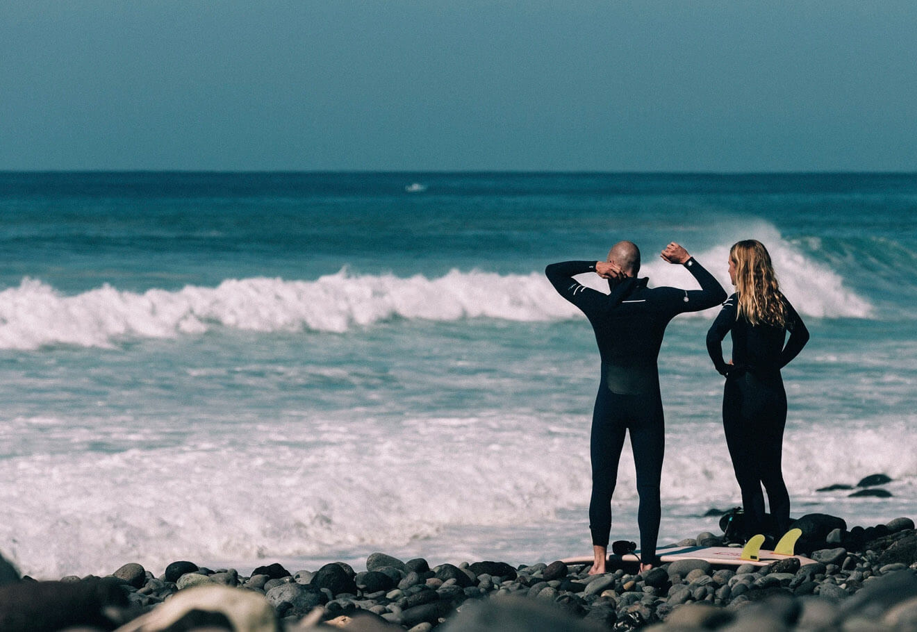 Two surfers in wetsuits