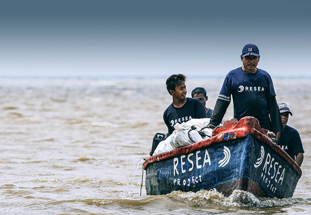 Fishermen from ReSea Project collect ocean litter on a boat