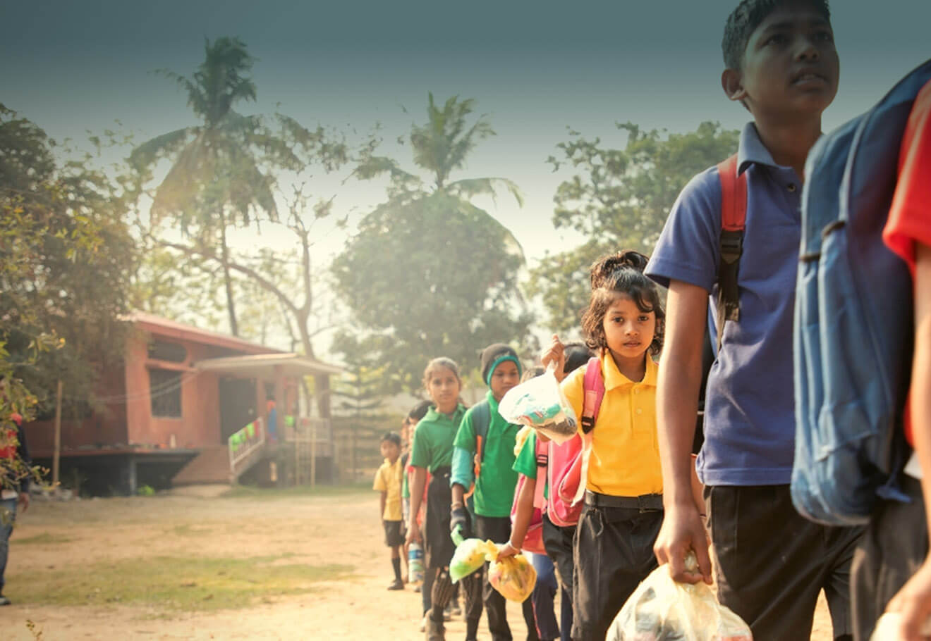Children lining up to get into school, bringing their recycling to cover school fees