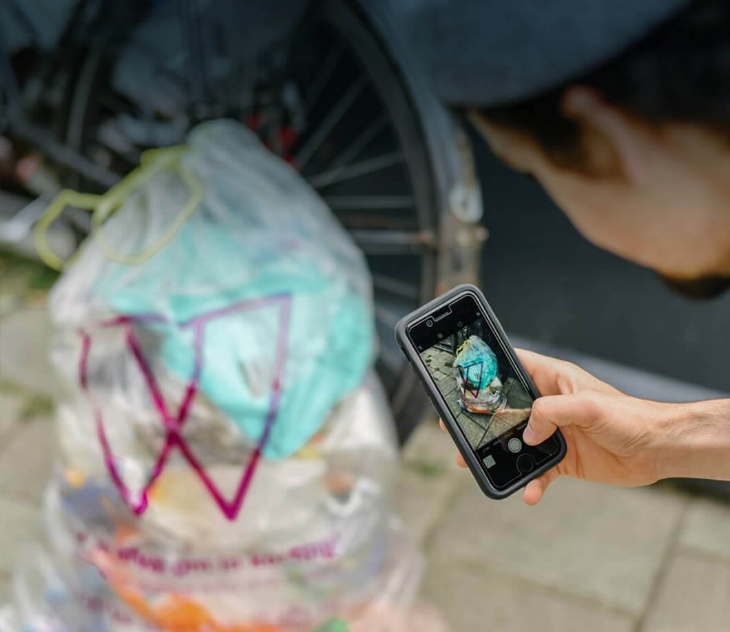 Person photographing recycling waste to earn rewards